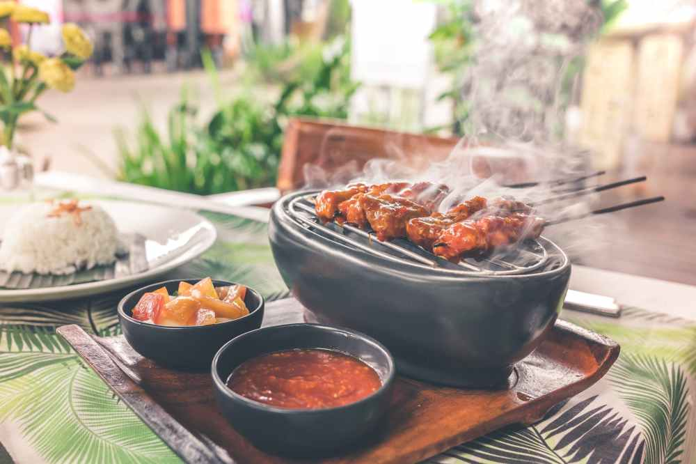 barbecue on grill with sauce platter